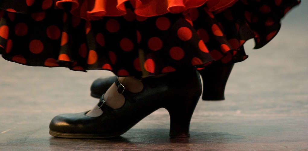 Close up images of feet of female flamenco dancer and black and red lunares patterned shirt hem